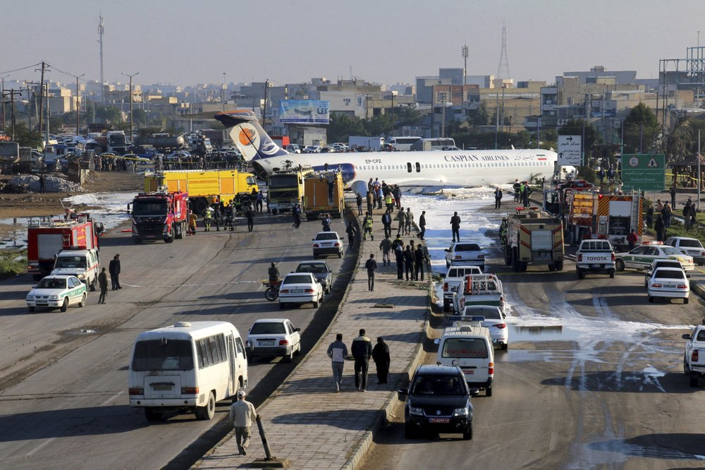 Passenger plane slides off slid off runway in Iran and onto highway