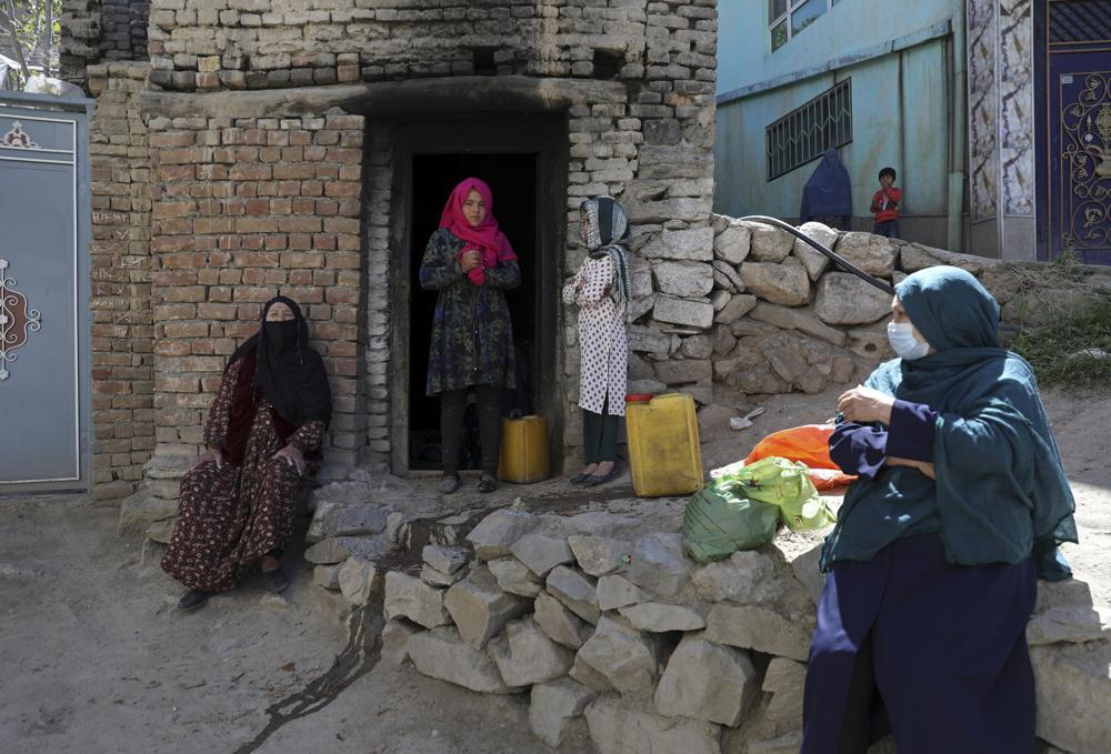 """IMAGE:Zarmeena, 13, stands in the door of her family's bakery in Kabul, Afghanistan, Saturday, April 24, 2021. Zameena has never been to school because her mother needs her in the bakery, though her younger brother, at 7, is in school. """"If I could go ... I would be a doctor,"""" she said. (AP Photo/Rahmat Gul)"""