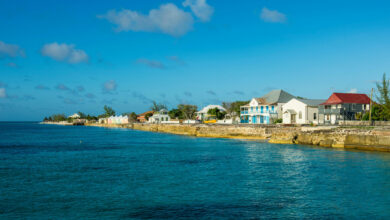 2AAWB2G Colonial houses in front of beach against blue sky during sunny day, Cockburn town, Grand Turk-Creator: Westend61 GmbH / Alamy Stock Photo Creator: Westend61 GmbH / Alamy Stock Photo | Credit: Alamy Stock Photo